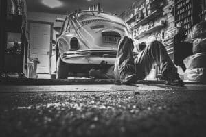 black and white photo of person working under VW bug in garage