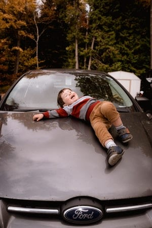 Photo of little kid laughing on hood of car