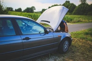 Car on side of country road with man looking under the hood