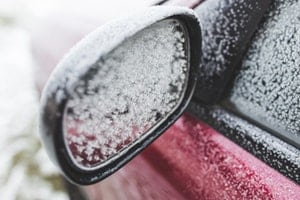 Frosty rear view mirror of red car