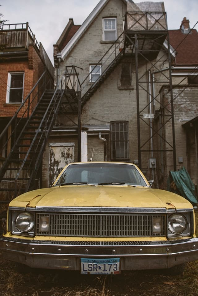Rusty old yellow car parked behind house