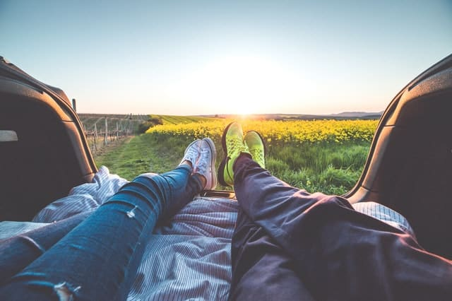Photo of couple's feet from back of hatchback looking out at field of flowers