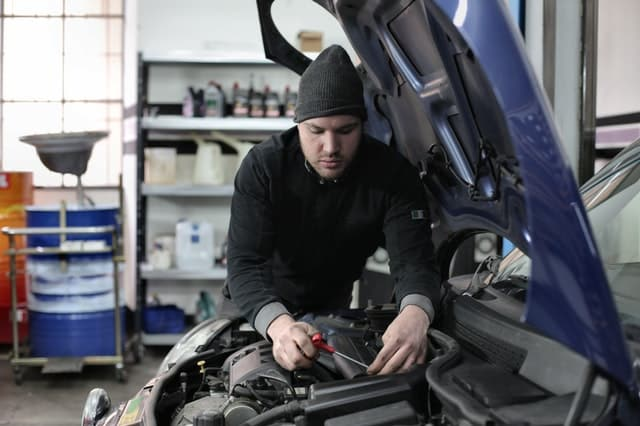 Man in beanie working on car engine