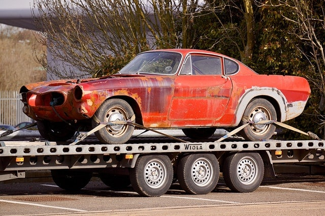 Junky red car on bed of tow truck