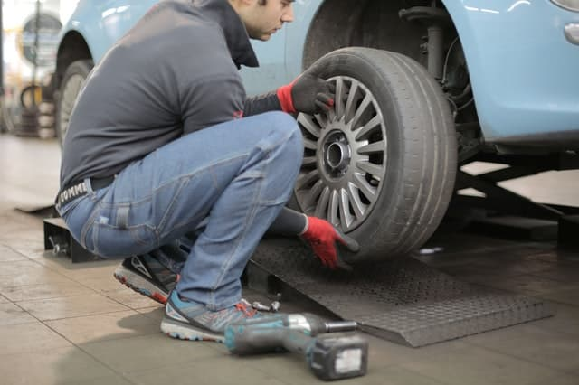 Man crouching next to blue car performing tire rotation