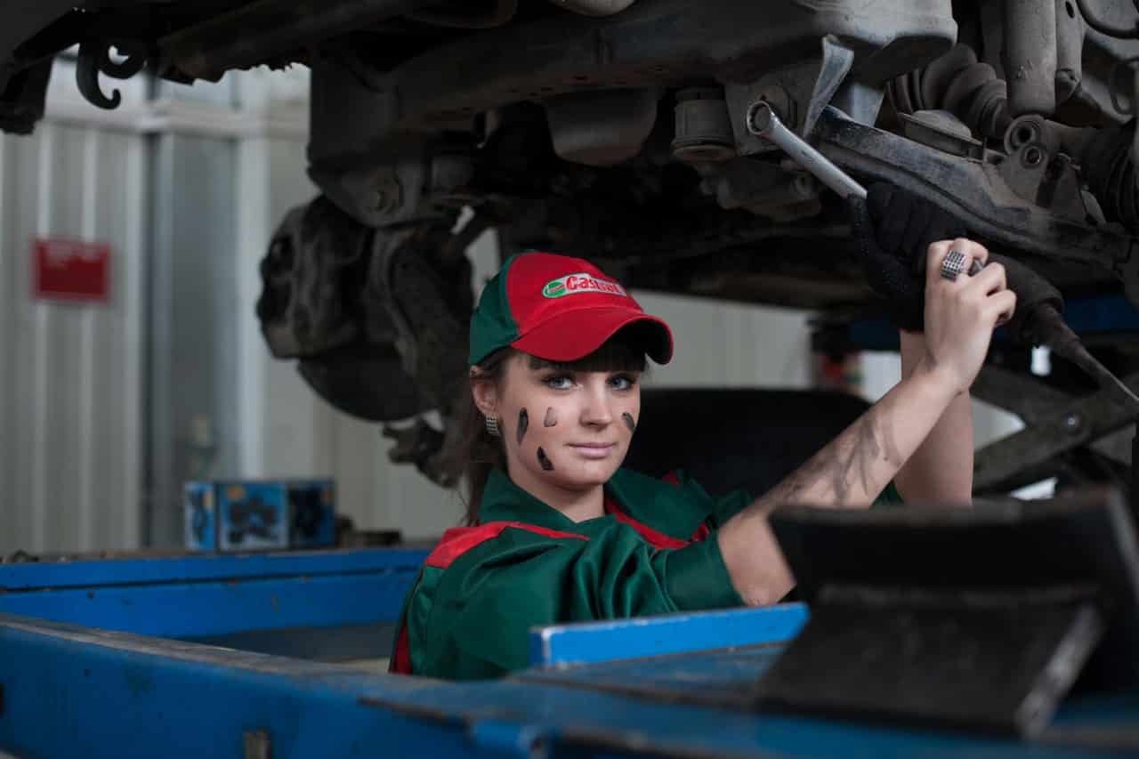 Woman in pit working on car